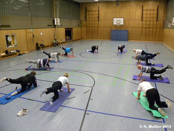 Die Herzsportgruppe in der Turnhalle bei Bodenübungen auf Matten